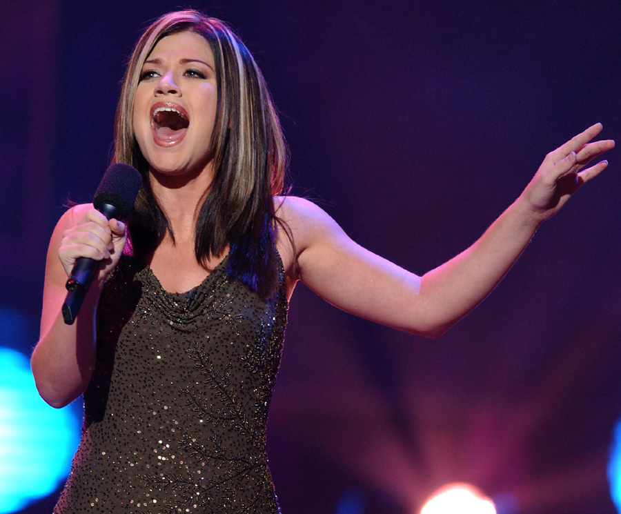 """Kelly Clarkson, 20, of Burleson, Texas, performs in a sing-off between two finalists for the title of """"American Idol,"""" in Los Angeles, Tuesday, Sept. 3, 2002.  The winner will be announced in the television show's finale on Wednesday, Sept. 4, after a phone-in vote, and rewarded with a RCA Records recording contract. (AP Photo/Lucy Nicholson)"""